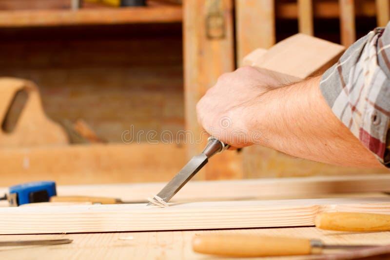 与凿子一起使用和雕刻工具的木匠的特写镜头 免版税库存照片