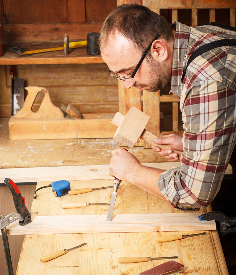 与凿子一起使用和雕刻工具的木匠的特写镜头 库存照片