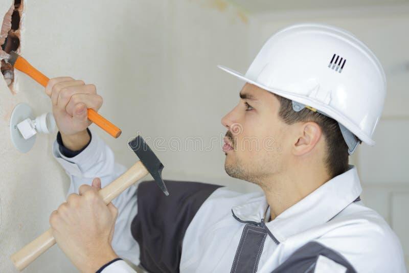 与凿子工作者的男性建造者打破的膏药 免版税库存照片