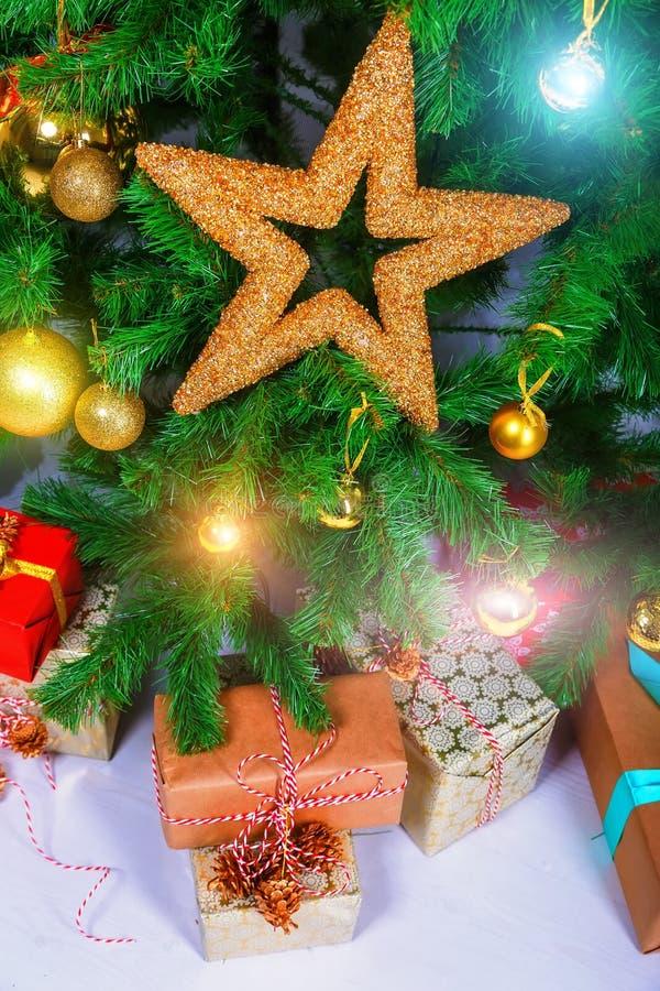 与分支的大圣诞节礼物和在一个木板的装饰星 库存照片