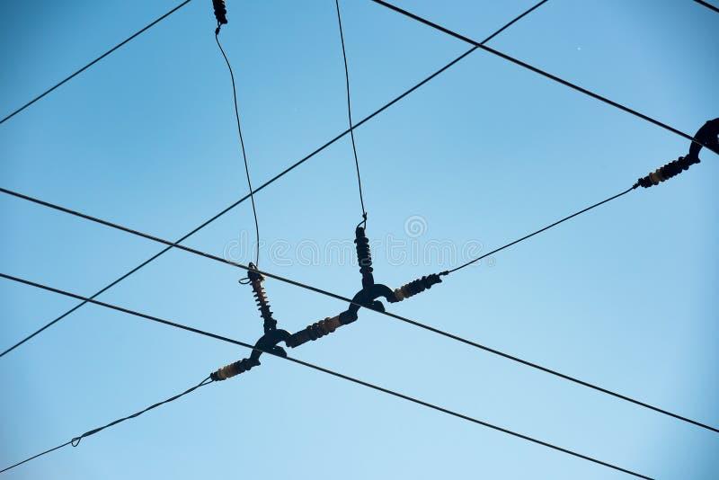 与分段绝缘器的相交的导线反对天空蔚蓝 库存照片