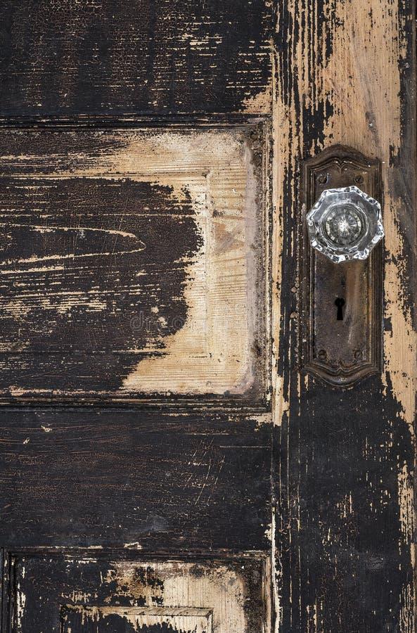与切削的剥的油漆和黑瓷门把和生锈的板材的老被风化的古色古香的破旧的木拼花板门 图库摄影