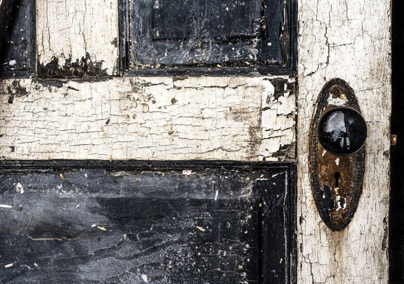 与切削的剥的油漆和黑瓷门把和生锈的板材的老被风化的古色古香的破旧的木拼花板门 免版税库存图片