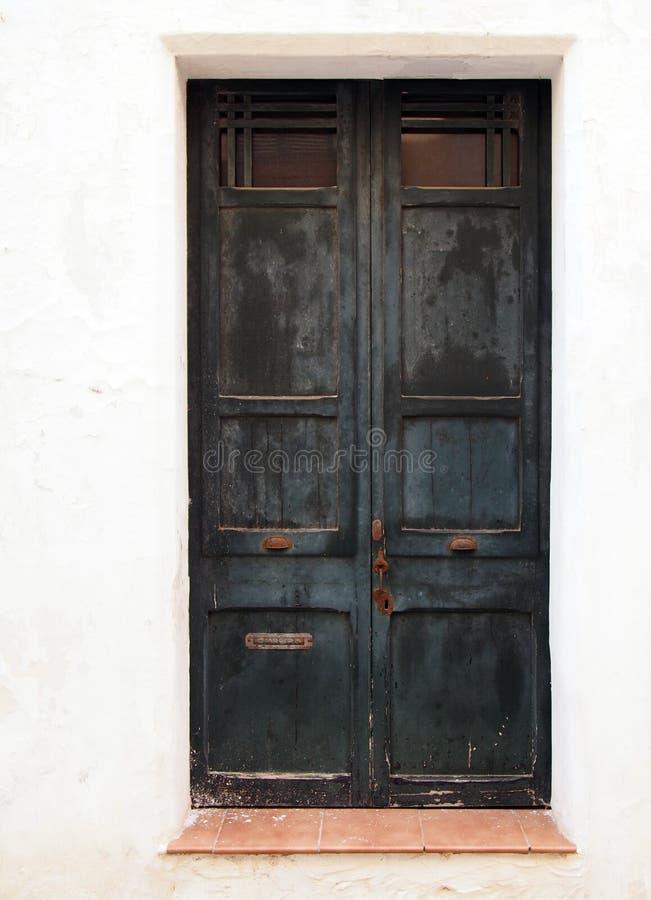 与切削的剥落的退色的剥的油漆和生锈的把柄锁和信箱的老木黑双门在白色被绘wal 库存照片