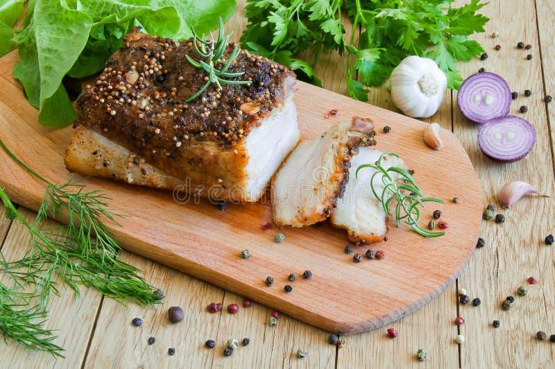 与切好的切片的被烘烤的烟肉在有菜和g的一个委员会 免版税库存图片