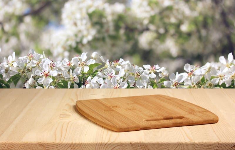 与切板的木桌在春天被弄脏的背景 库存照片