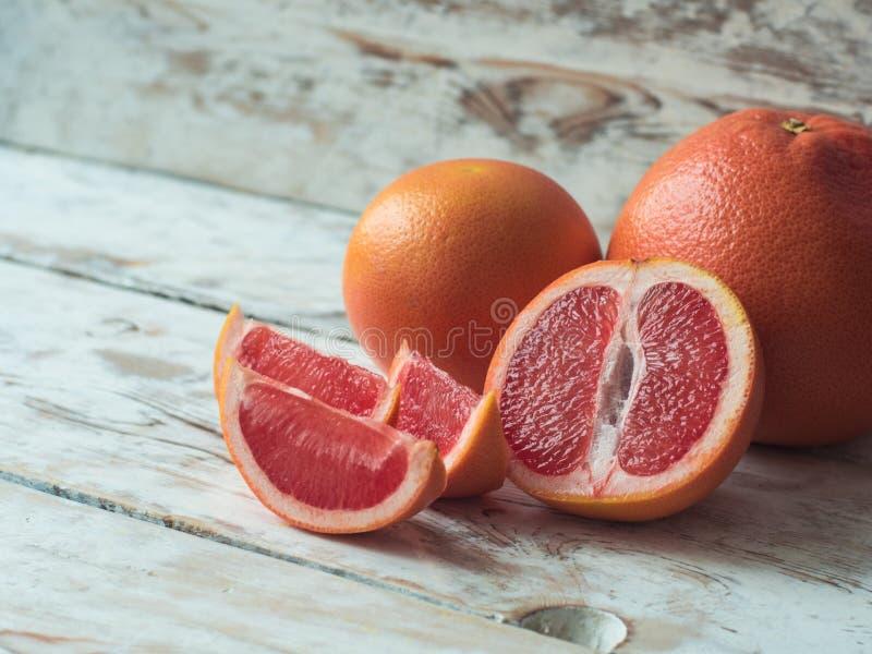 与切片在一张木桌上,关闭的葡萄柚 免版税库存图片