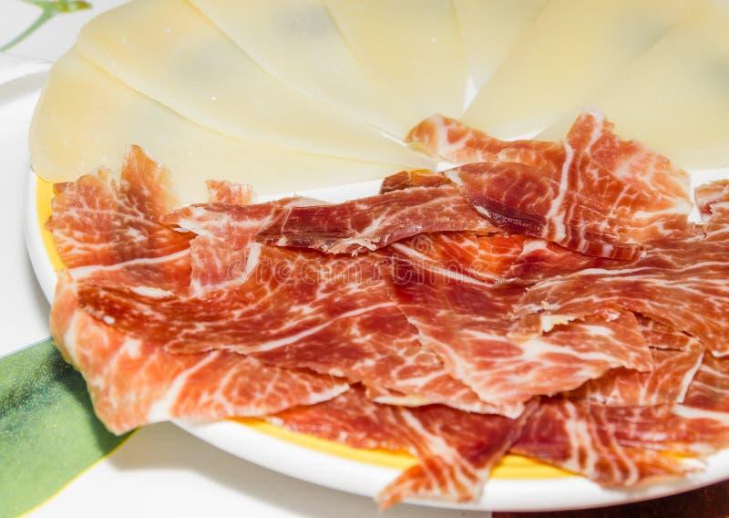 与切片的典型的西班牙塔帕纤维布serrano火腿和manchego che 免版税图库摄影