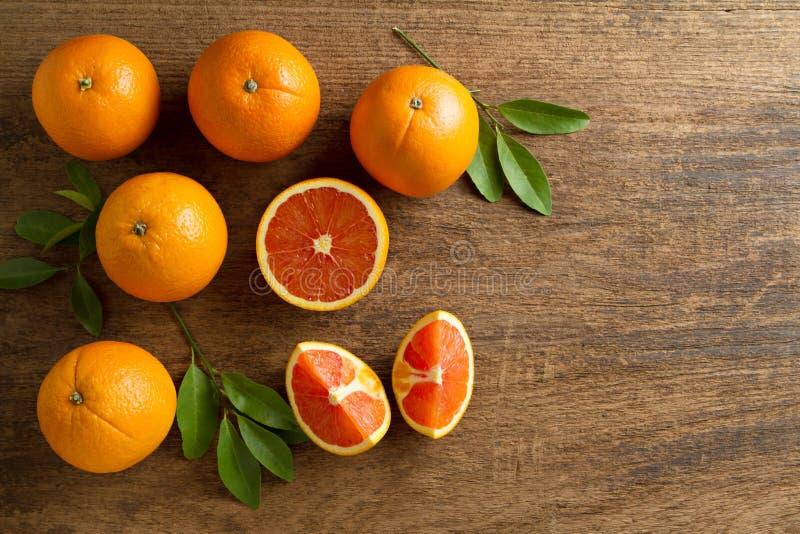 与切片的新鲜的在木背景的桔子和叶子 免版税库存图片