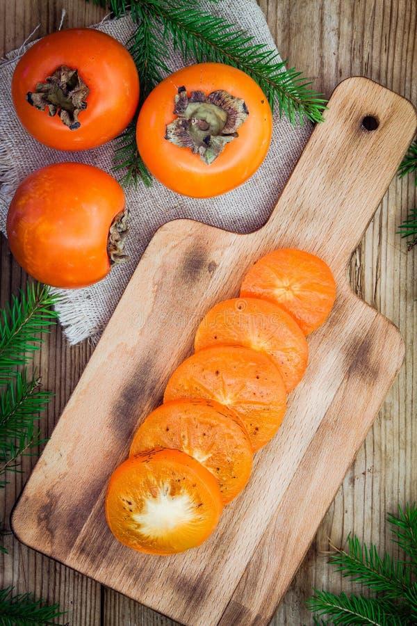 与切片的新鲜的有机柿子在木板 库存图片