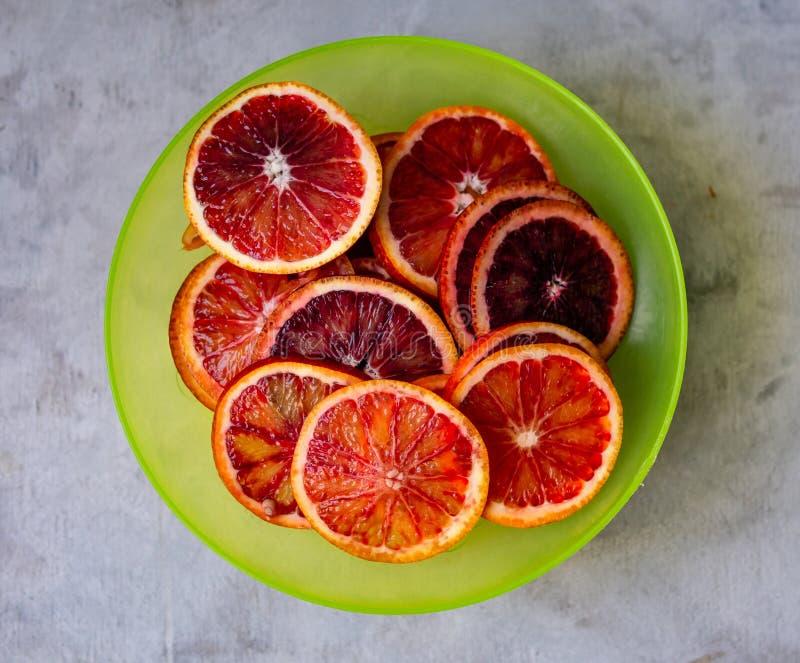 与切片的新鲜的红色血橙在灰色背景的绿色板材 顶视图,选择聚焦 库存照片