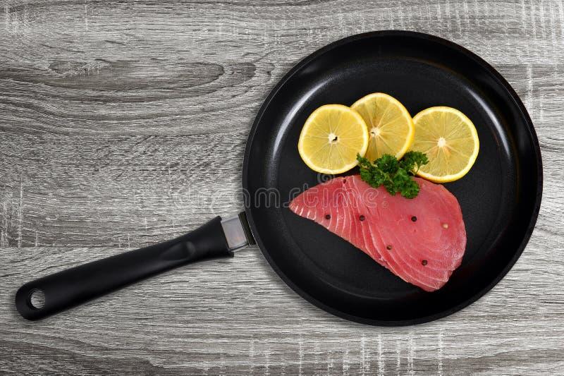 与切片的新鲜的金枪鱼排在长柄浅锅的柠檬 免版税图库摄影