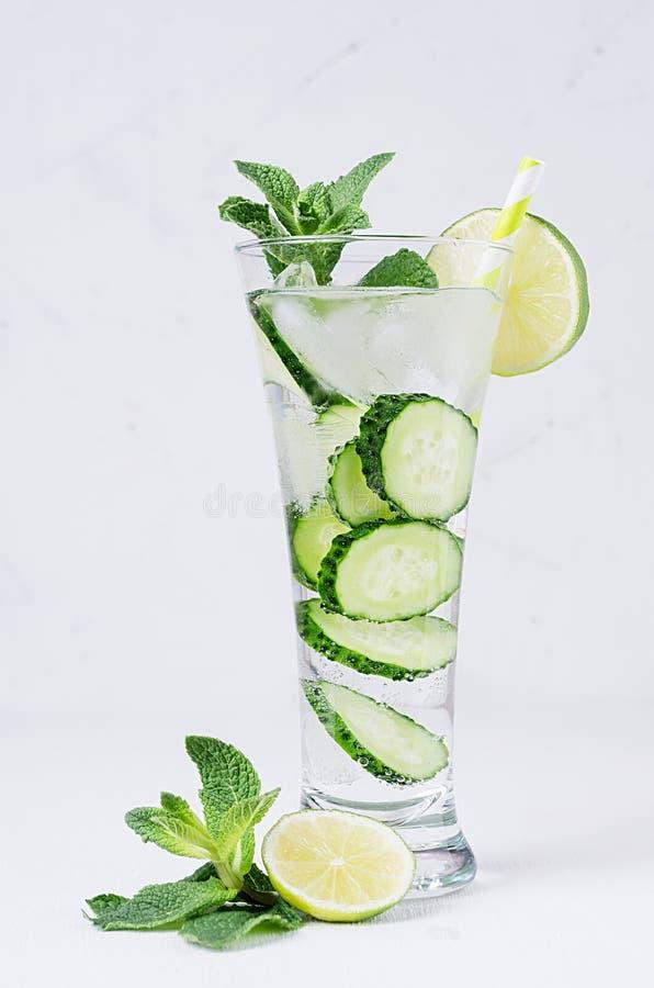 与切片黄瓜,冰,石灰,在白色木桌上的薄菏的透明有机饮料 免版税库存图片