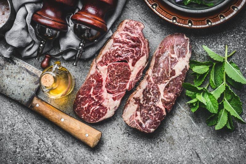 与切肉刀和调味品的两块干年迈的未加工的牛排在黑暗的土气具体背景 免版税库存图片