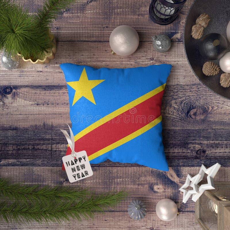 与刚果旗子的新年快乐标记在枕头 在木桌上的圣诞装饰概念与可爱的对象 库存照片