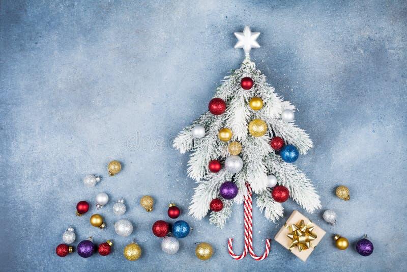 与创造性的圣诞节杉树装饰的星、礼物盒和五颜六色的球的贺卡在蓝色背景顶视图 平的位置 免版税图库摄影