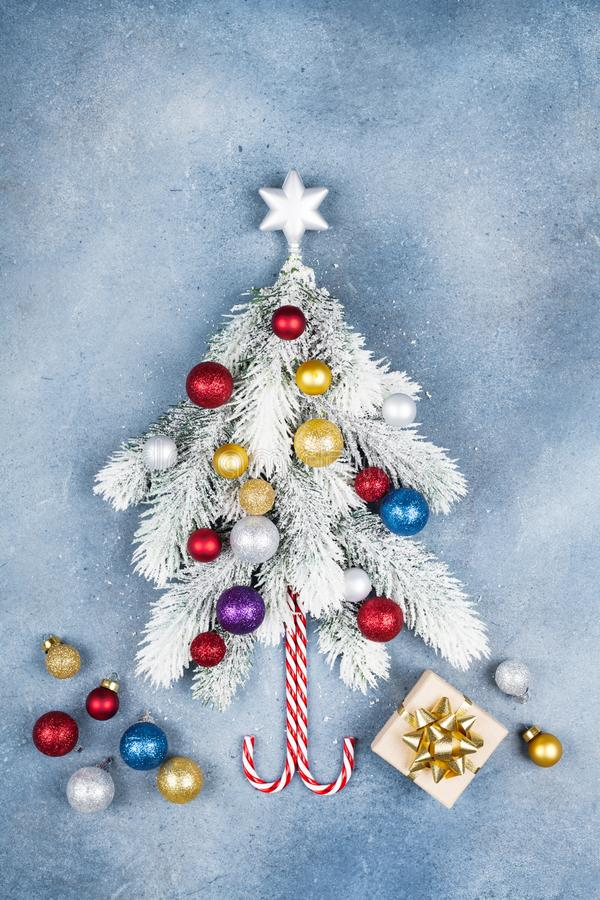 与创造性的圣诞节杉树装饰的星、礼物盒和五颜六色的球的贺卡在蓝色背景顶视图 平的位置 库存图片