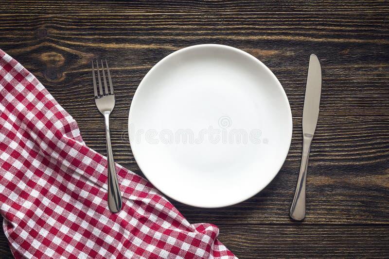与利器的土气桌设置和在da的红色方格的餐巾 免版税图库摄影