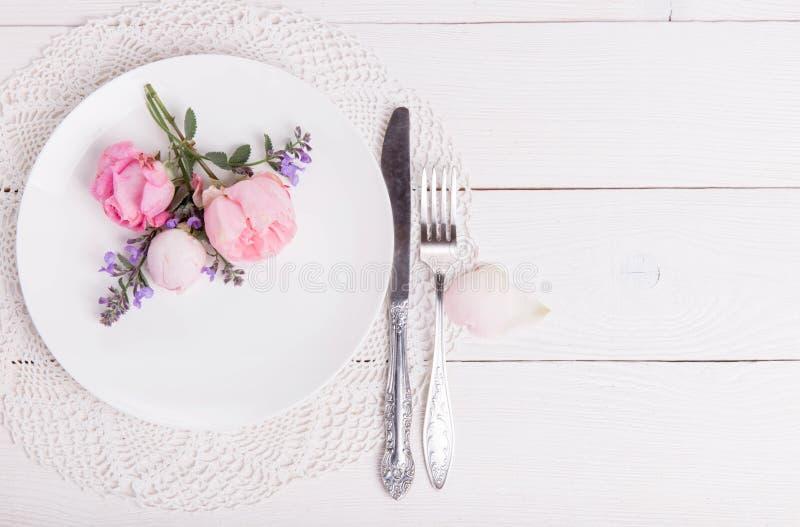 与利器,一点的欢乐桌设置上升了和在桃红色桌上的心脏 顶视图 免版税库存图片