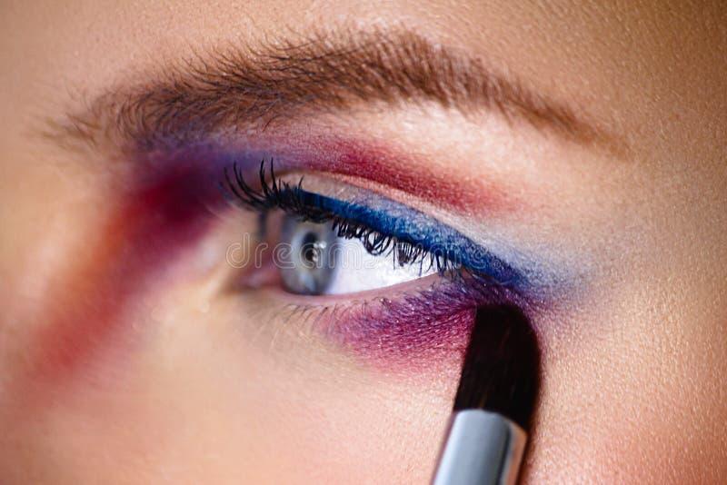 与刷子的ПMake-up艺术家applaying的颜色眼影膏 特写镜头p 库存图片