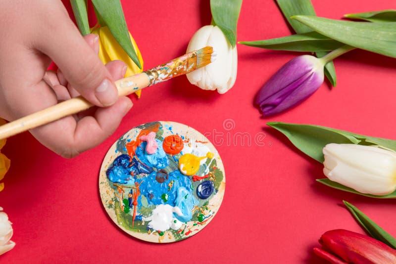 与刷子的女性手绘画在郁金香花附近的白色郁金香在红色背景 背景概念花春天空白黄色年轻人 免版税库存图片