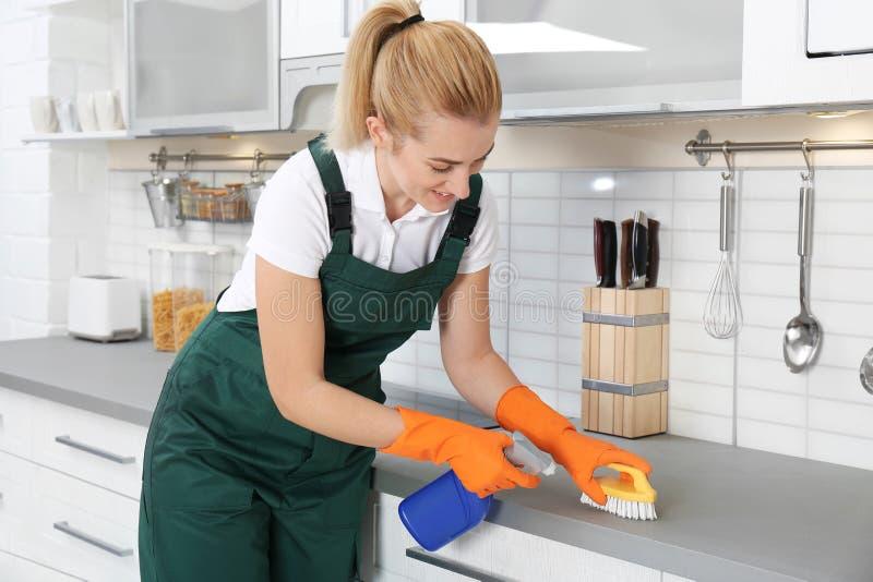 与刷子的女性管理员清洁厨台 库存图片