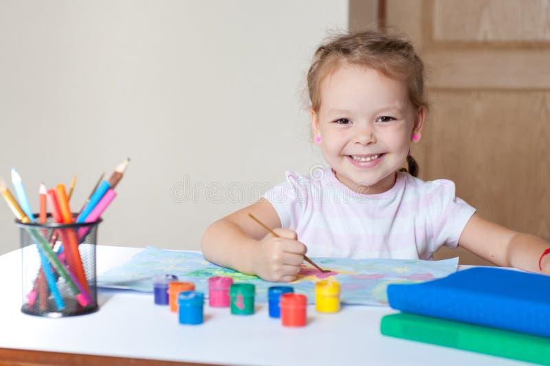 与刷子的小的逗人喜爱的女孩绘画 免版税图库摄影