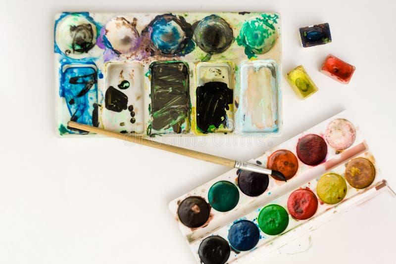 与刷子的明亮的五颜六色的水彩在白色背景的油漆和调色板 特写镜头水彩盘子 E 库存照片