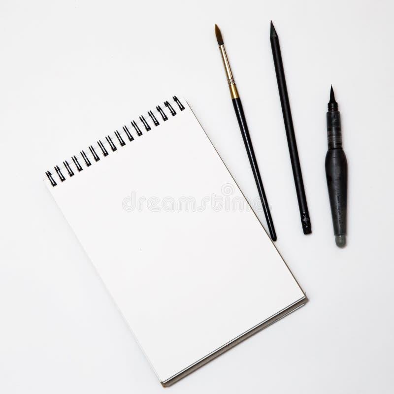 与刷子的空的白皮书在黑白背景 免版税库存图片