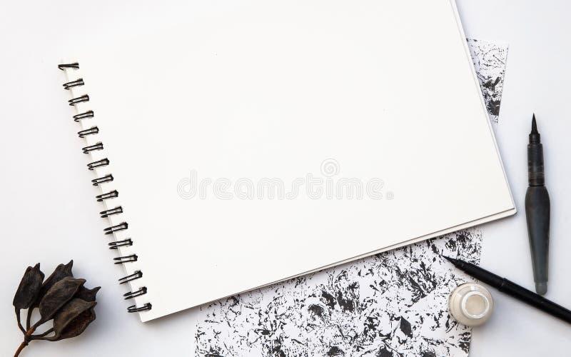 与刷子的空的白皮书在黑白grangy背景 库存图片