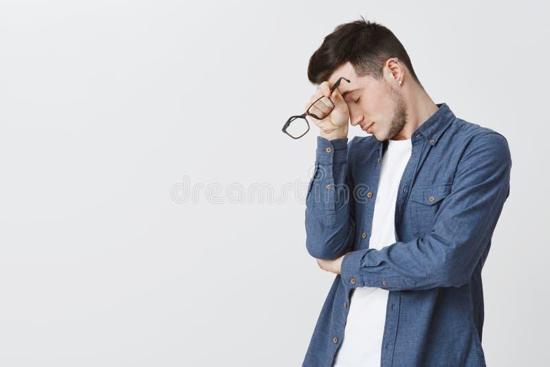 与刺毛的有吸引力的年轻男性模型和被刺穿的耳朵向左转的倾斜的头在手边作为感到疲乏,闭合值 免版税图库摄影