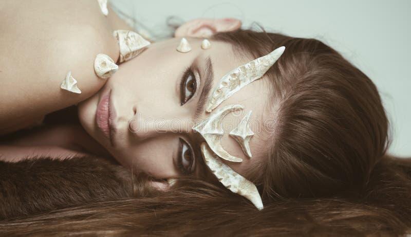 与刺的童话生物在说谎在黑毛皮地毯的皮肤 有狡猾看起来吸引的人民的女性恶魔 女孩 库存照片