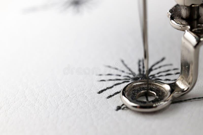 与刺绣机器-在白色人造皮的dandilon的刺绣-接近  免版税库存照片