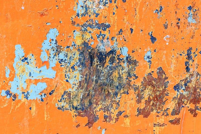 与削皮油漆和蓝色斑点的金属橙色背景和 库存图片