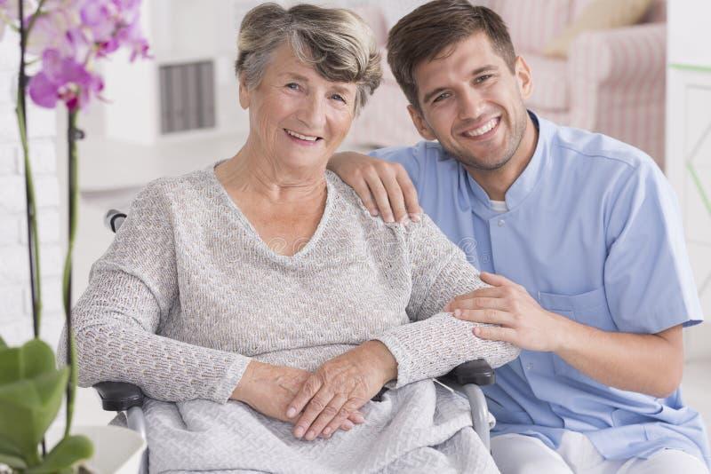 与前辈的微笑的护工在休养所 免版税库存照片