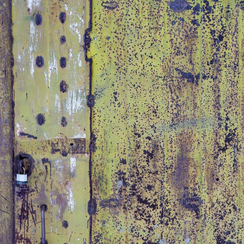 与剥绿色油漆的老金属门 金属生锈的表面 免版税库存照片