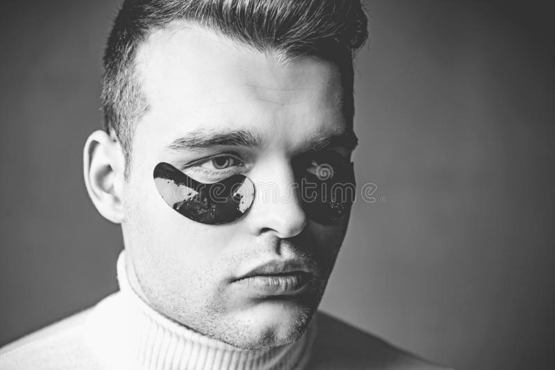与剥落的人面孔在眼睛下 供以人员剥落 在接近的眼睛下的补丁人的 针压法,按摩他的寺庙 库存图片