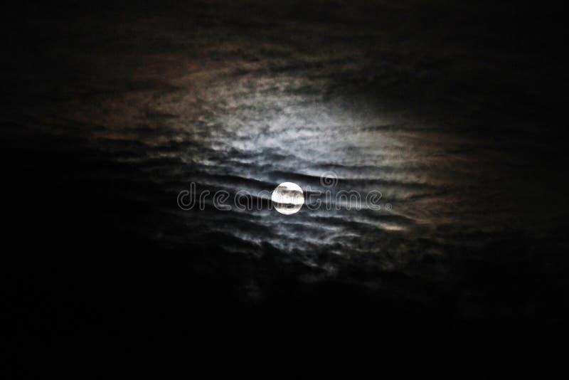 与剧烈的云彩和月球光晕背景的满月 免版税图库摄影