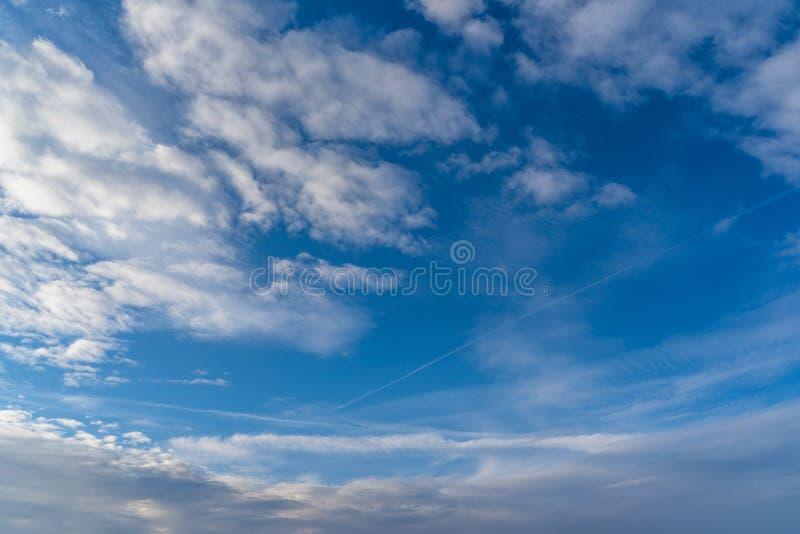 与剧烈的云彩形成的天空蔚蓝在晴朗的冬日-摘要 免版税库存照片