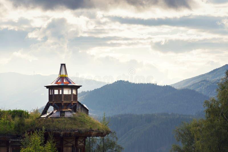 与剧烈的云彩的美好的日落在Dachstein山,与绿色草皮屋顶的木监视 图库摄影