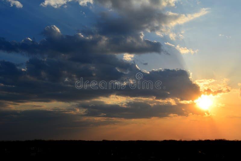 与剧烈的光的美丽的日落天空 与乌云和太阳的Cloudscape 免版税库存图片