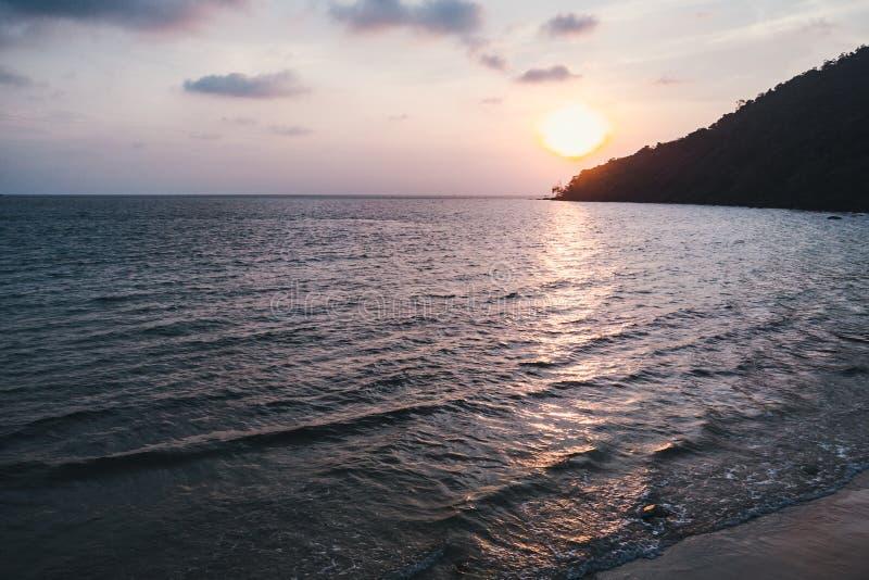 与剧烈的多云天空的美好的风景风景在波纹海水的日落和太阳沼地在西哈努克ville,海湾  免版税库存照片