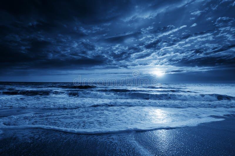 与剧烈的天空和起伏式波的午夜蓝色沿海月出 免版税图库摄影