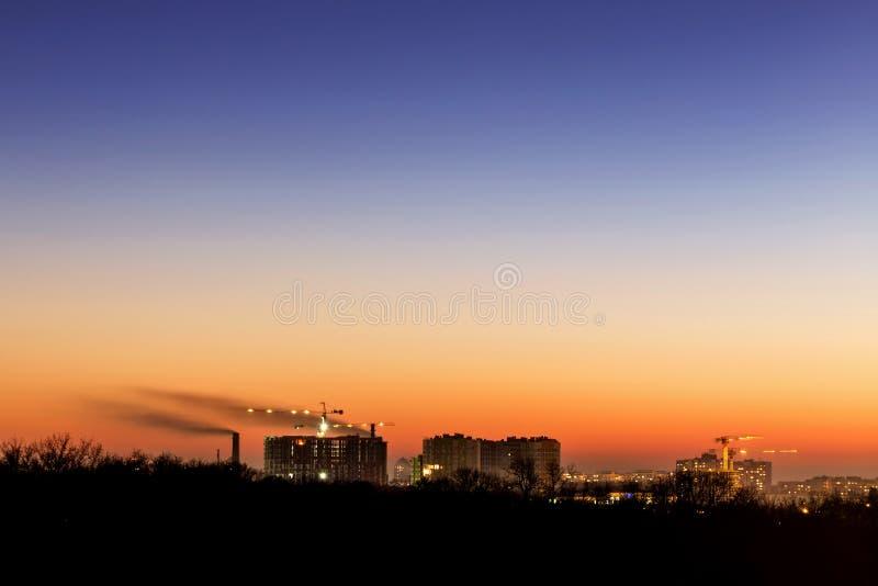 与剧烈的天空日落的都市风景 大厦和烟斗剪影  都市工业城市 危机生态学环境照片污染 免版税图库摄影