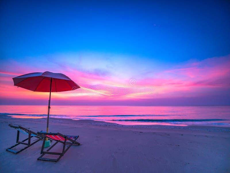 与剧烈的早晨天空在海有椅子的和伞的日出在海滩 免版税图库摄影