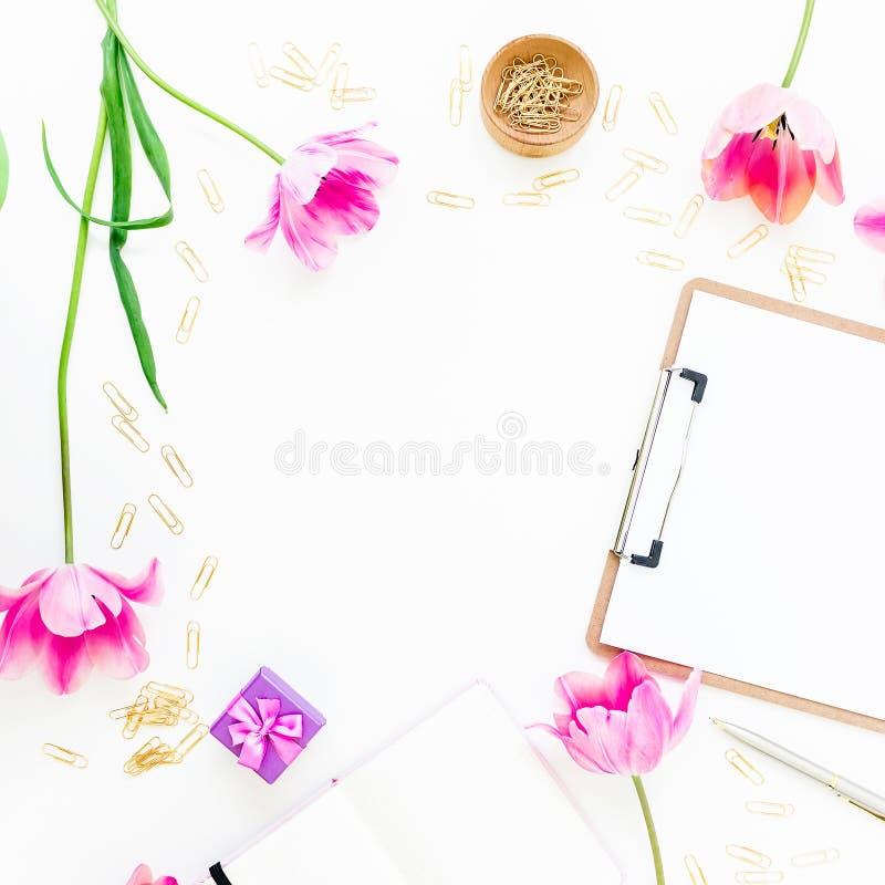 与剪贴板、化妆用品、桃红色郁金香和辅助部件的家庭办公室工作区在白色背景 来回的框架 平的位置,顶视图 图库摄影