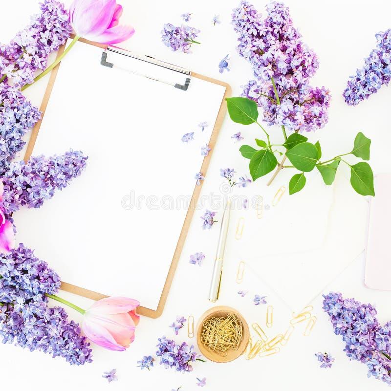 与剪贴板、淡紫色花和辅助部件的女性构成在白色背景 春天…上升了叶子,自然本底 平的位置,顶视图 库存图片