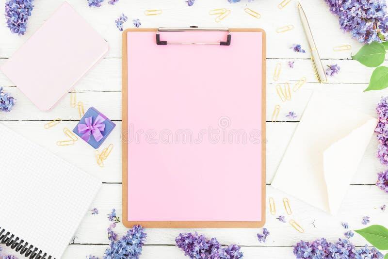 与剪贴板、笔记本、淡紫色花、礼物盒和辅助部件的女性职场构成在土气背景 平的位置, 库存照片