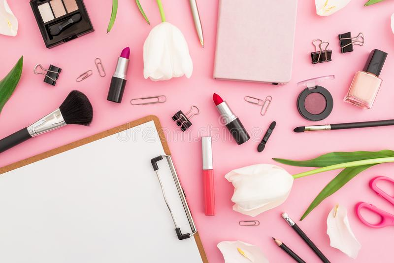 与剪贴板、郁金香花、化妆用品和辅助部件的秀丽构成在桃红色背景 顶视图 平的位置 家庭女性d 免版税库存照片