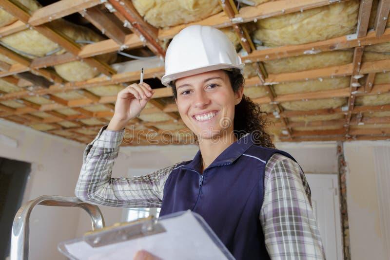 与剪贴板的愉快的女性建造者 图库摄影
